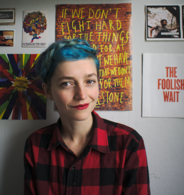 Image of a mid-20s girl with blue hair standing in front of some posters. The girl is me.